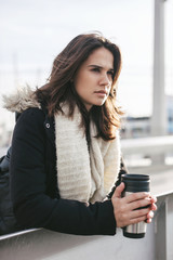 Young woman with winter clothes holding a coffee thermos on a dock.