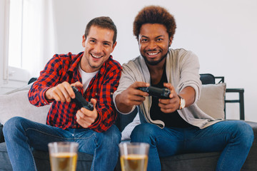 Two happy young friends playing video games at home.