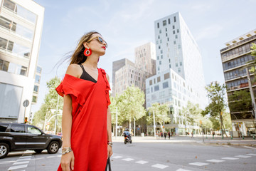 Lifestyle portrait of a woman in red dress standing outdoors at the modern business district in Barcelona city