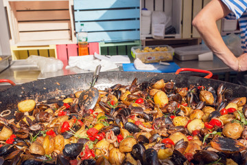 Kitchen with big plate of cooking fresh food with oysters, potato and spices. Seafood market dish