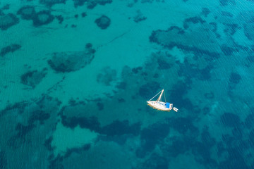 Beautiful beach, coast and bay with crystal clear sea water and a sailing yacht seen from above