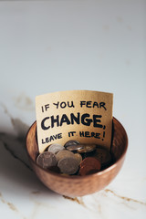 "Copper bowl with coins with sign ""If you fear change, leave it here"""