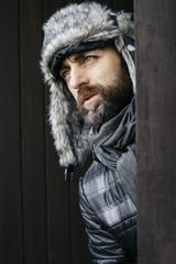 Portrait of a man looking away wearing a winter furry hat