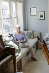 Senior Woman working on mobile tablet at Home