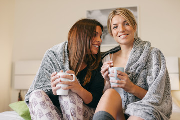 Two women roommates keeping warm with cozy blanket and drinking coffee at home.