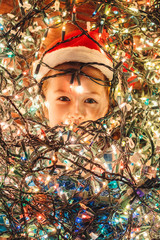 Young Girl Under a Pile of Christmas Lights