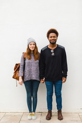 Portrait of young multi ethnic couple standing on white background.