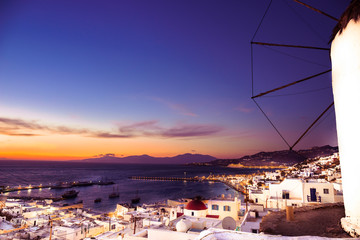 view of Mykonos, windmill and old port with cruise ship at sunset
