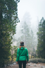 A woman in a green puffy jacket in a forest.