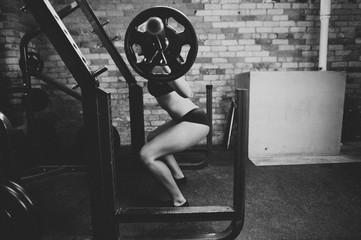 Female bodybuilder doing back squats in gym