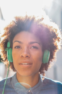 African american woman listening to music with green headphones in the street.