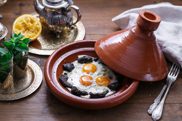 Fried eggs and beef in tajine dish with cover, Moroccan breakfast