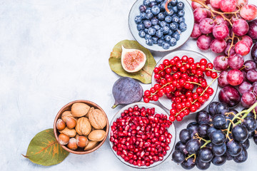 Berries and fruits, nuts healthy antioxidant red and purple food top view text space.