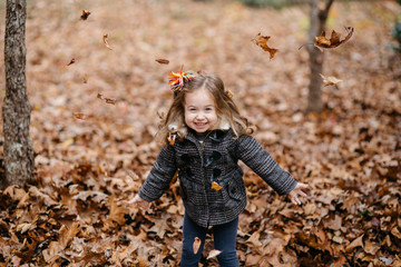 Happy toddler throwing leaves outside
