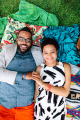 A hipster African American couple laying on blankets in the park