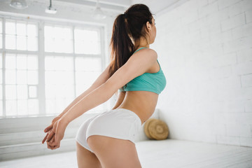Part of fitness body. Fitness woman stretching her waist. Sports and fitness - concept of healthy lifestyle. Fitness woman in the gym. Spin muscles