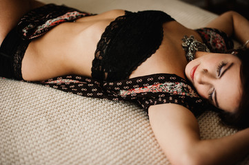 Young bohemian woman in black lace underwear lying on bed