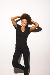 Portrait of afro american woman wearing black clothes against white background.