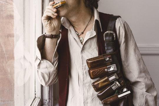 Man playing harmonica in window while wearing leather harmonica belt