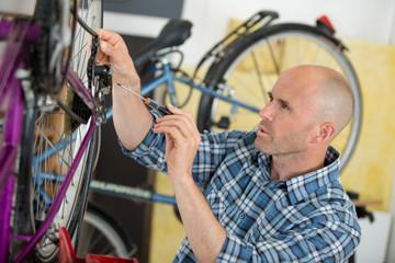 man reparing bike in the bicycle repair shop