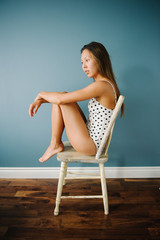 Young attractive mixed asian girl in boudoir polka dot body suit sitting in chair
