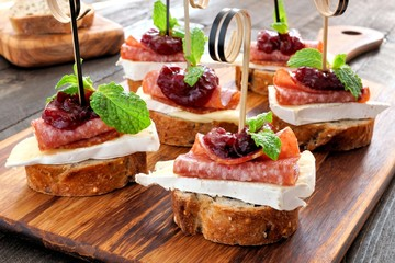 Spoed Fotobehang Voorgerecht Holiday crostini appetizers with cranberry sauce, brie, salami, and mint on a wooden server