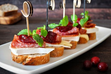 Spoed Fotobehang Voorgerecht Holiday crostini appetizers with cranberry sauce, brie, salami, and mint on white serving plate against rustic wood