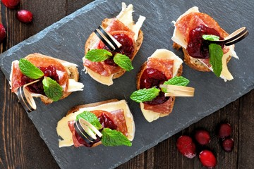 Holiday crostini appetizers with cranberry sauce, brie, salami, and mint above view on a slate server