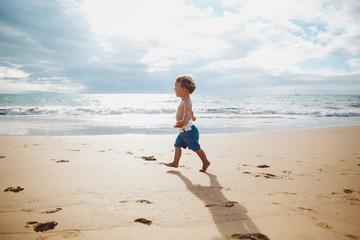 Toddler boy running on sandy tropical beach alone