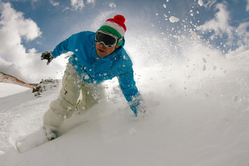 Young man snowboarding in powder snow