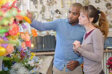 Man and woman looking at memorial flowers