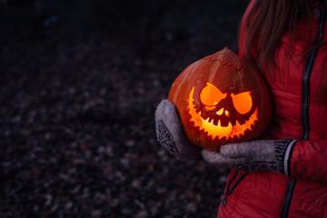Woman holding carved halloween pumpkin