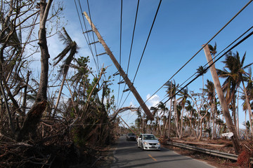 Cars drive under a partially collapsed utility pole, after the island was hit by Hurricane Maria in September, in Naguabo