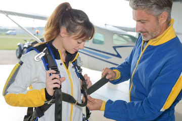 instructor fastening harness on female parachutist