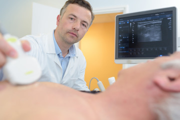doctor placing ultrasound probe on male patients chest