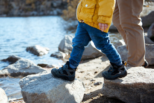Father and son walking on the rocks near the lake.
