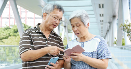 Retired couple using mobile phone at outdoor
