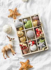 Wooden box of vintage christmas decorations on the light background, top view. Christmas still life