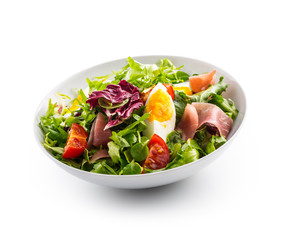 Salad Isolated on White. a bowl of fresh lettuce salad with tomatoes eggs prosciutto over white