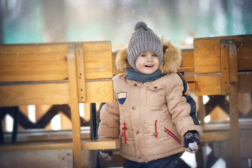Portrait of a boy with a smile  and winter clothes between the benches during a snowfall