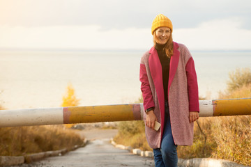 Young beautiful brunette woman in yellow knitted headband, pink coat and jeans smiling and posing outdoors on a fall day while walking