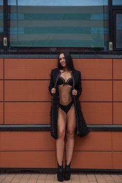Young beautiful woman in black underwear and classic black high-heeled coat posing posingly on the rim of a modern orange building on the street