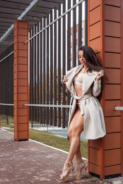 Young beautiful woman in white lingerie and classic beige high-heeled coat posing posingly in front of a modern orange building on the street