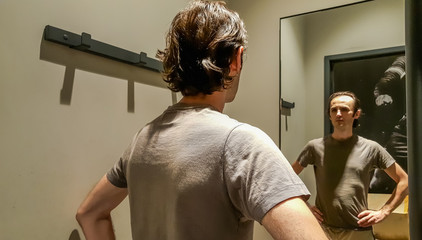 Rear view of a young Caucasian handsome man trying new clothes in front of a mirror in a changing room of a clothing store