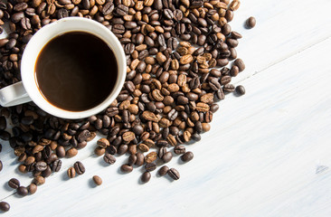 a cup of coffee with coffee seed on white wood background