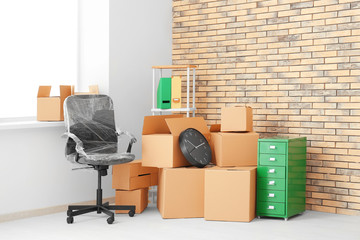 Office move concept. Carton boxes and furniture in empty room