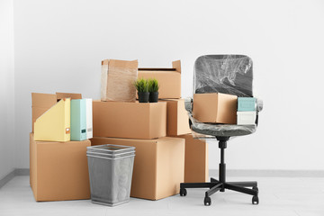 Office move concept. Carton boxes and chair on floor in empty room