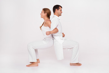 Yoga class paired with the coach. Man and woman doing the exercise.