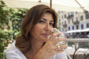 Donna al ristorante beve vino