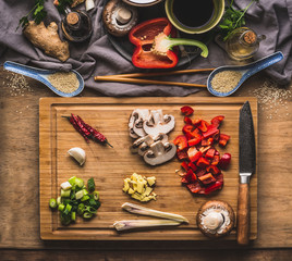 Chopped vegetables for stir fry cooking on wooden cutting board on kitchen table background with ingredients, top view. Asian food and eating , Chinese or Thai cuisine concept